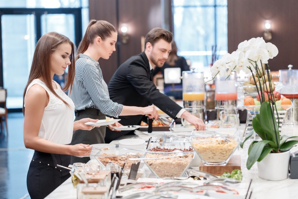 Everything is so fresh and tasty. Two businesswomen and a businessman standing by the catering table and taking dishes for the business lunch