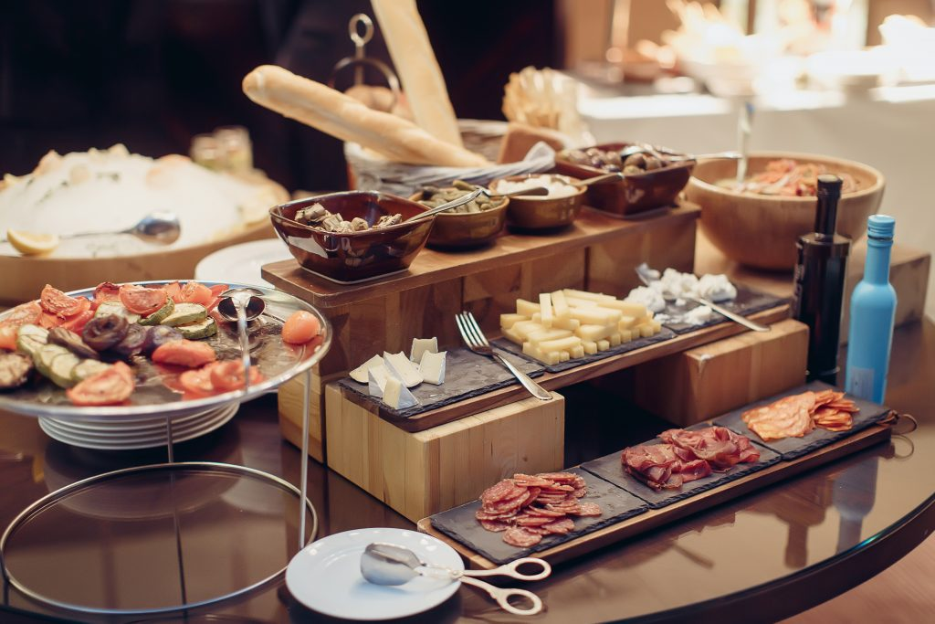 Buffet with antipasti snacks with cheeses with jamon meat, olives and salads. Breakfast buffet with salad and olive bread jamon on a thick wooden board with a knife and souce. Soft focus.